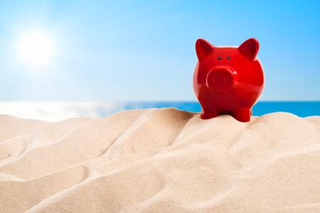 On the beach - a piggy bank on a sand dune