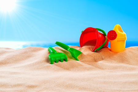 On the beach - sand toys on a sand dune in front of beautiful azure sea on a sunny day Stok Fotoğraf