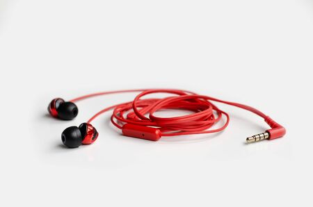 Red headphones rolled up on a white background
