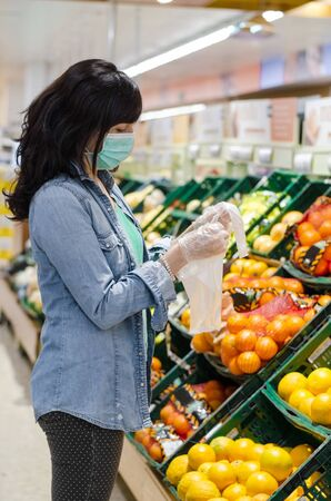 Woman buying fruit in a supermarket with a green mask. Opening a plastic bag