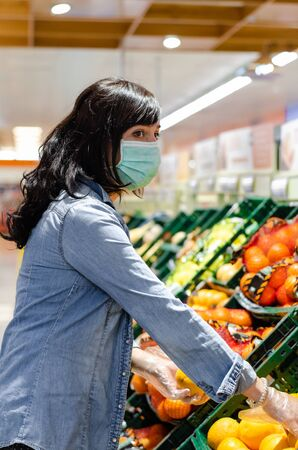 Woman buying fruit in a supermarket with a green mask