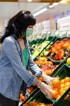 Woman buying fruit in a supermarket with a green mask. Picking up an orange