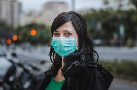 Woman wearing a green mask on the street. Living a normal life