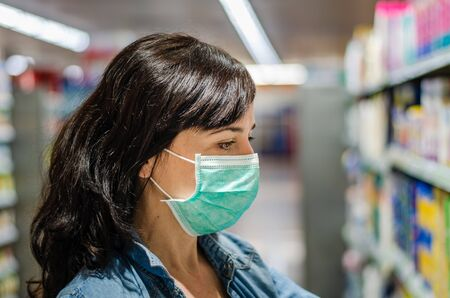 Woman shopping with a green mask in a supermarket 写真素材