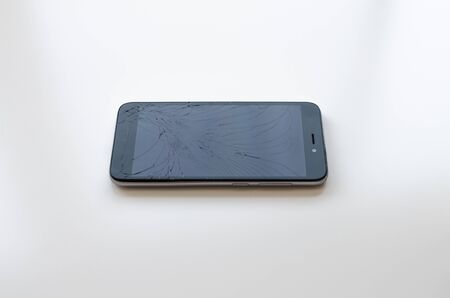Cell phone with broken screen in a white background 写真素材