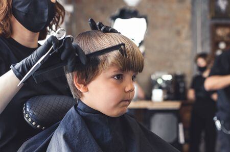 Serious blond boy being styled in hairdressing salon by a female hairdresser with a mask