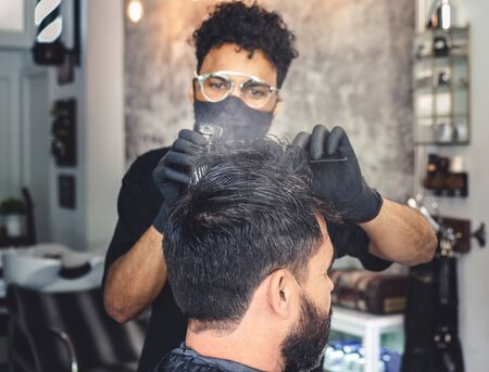 Mulatto barber with a mask wetting a client's hair with a sprayer from the background 写真素材
