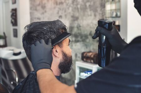 Barber wetting a client's hair with a sprayer from the background