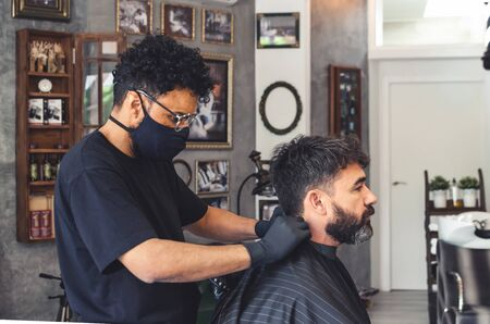 Mulatto barber putting neck cover paper in a barbershop. Client with beard. 写真素材