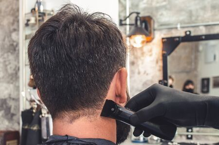Barber cut hair on neck and nape of man in barbershop with professional clipper tool. Electric trimmer machine cutting hair on client skin 写真素材