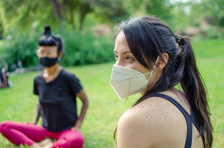Two women talking in a park with face masks. They are sitting on the grass