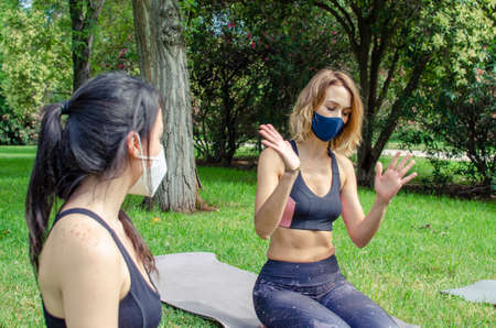 Woman explaining a problem to a friend in a park wearing face masks
