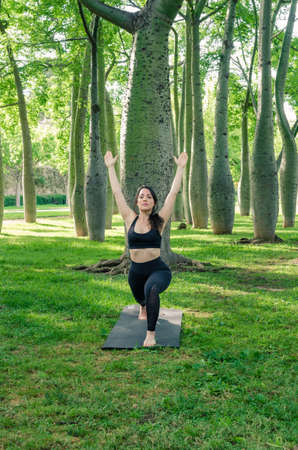 A woman doing yoga in the park. Exercising the virabhaddrasana pose 写真素材