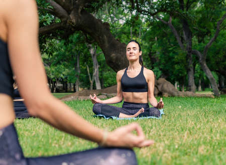Two women meditating in the padmasana yoga pose in the park