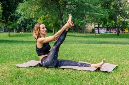 Young woman doing yoga in the park. Krounchasana pose