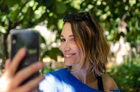 pretty young woman taking a selfie while smiling. She wears sunglasses over his head