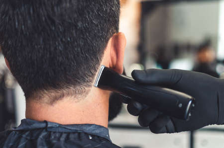 Barber cut hair on neck and nape of man in barbershop with professional clipper tool. Electric trimmer machine cutting hair on client skin. Close up 写真素材
