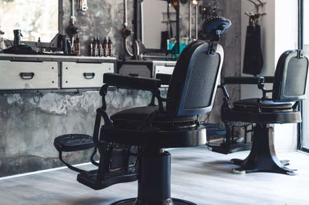 Two black leather and iron barber chairs in an old style barber shop