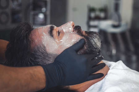 Hairdresser wearing latex gloves giving a facial to a handsome bearded man.