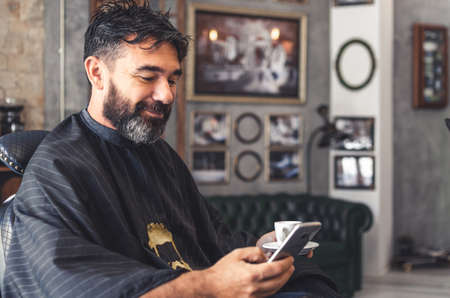 Barbershop customer using a cell phone while having coffee 写真素材