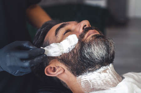 barber with latex gloves applying cream with a brush to a client to shave the beard