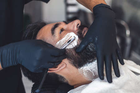 barber in latex gloves shaving a handsome man with a knife
