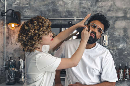 girl pretending to shave a bearded man in an old style barbershop
