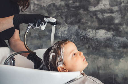 hairdresser wearing black latex gloves rinsing a child's hair after washing