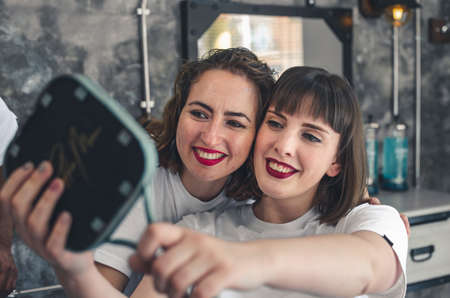 Two girls looking in the mirror smiling in a barbershop