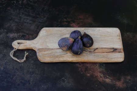 four organic figs on a wooden board.