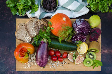 Assortment of fresh vegetables and fruits on a wooden board
