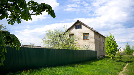 Two-storey House behind the Green Fence in Small City Stock Photo