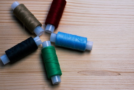 sewing machines: 5 coils with a thread on a wooden table