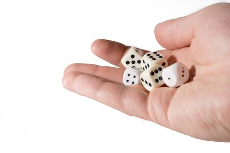 The dice game: hand throwing game cubes, isolated on white background. Close-up of a human hand holding five dice