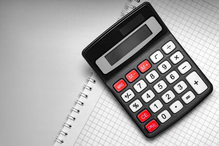 White notebook and digital calculator with red buttons on a white table, isolate.