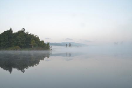 Island in foggy lake
