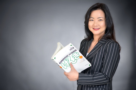 asian teacher holding a book Stock Photo
