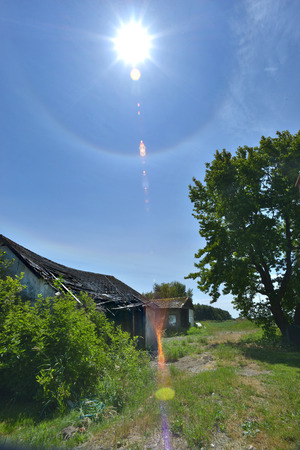 worn structure: old shack with sun dog - lens flare Stock Photo