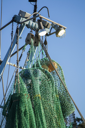 Nets suspended from the rigging of a fishing trawler. Standard-Bild - 118703786