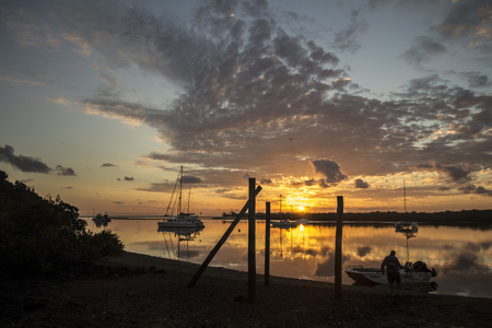 A fisherman launching his boat at sunrise at Riverview dirt boat ramp in the Elliott River in Queensland, Australia. Editorial