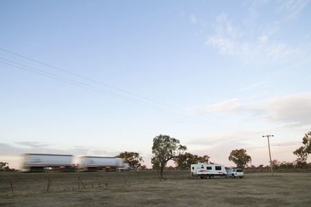 A heavy road truck drives past a camp site in the Australian outback. While free or low cost campgrounds are popular with caravaners they are often close to noisy highways. 報道画像