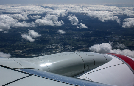 View looking over the jet engine and down through the clouds from the window of a commercial airliner.