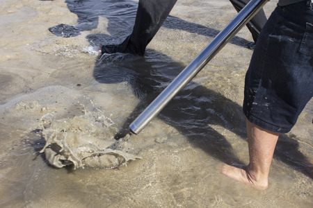 Fishermen use a bait pump to suck small crustaceans from deep in the river sand in Queensland where they are called yabbies. In other areas the same crustaceans are called nippers. 版權商用圖片
