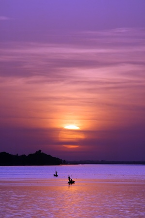 African fishermen on river with sun setting behind them photo