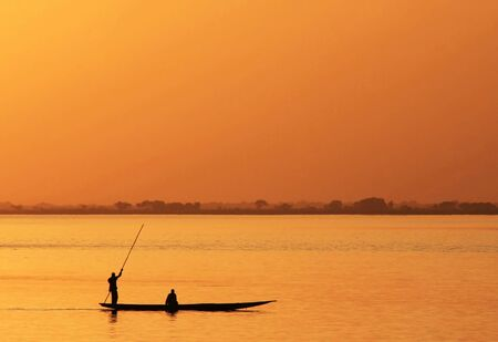 Silhouette of African fisherman in canoe at sunset photo