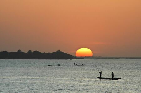 African fishermen silhouetted in canoes at sunset photo