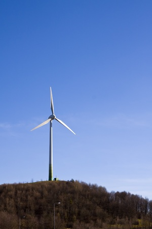 Lone standing wind turbine on a small wooded hill Stock Photo