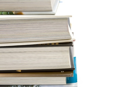 Stack of heavy hardback books over a white background