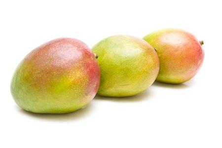Three ripe mangos over a white background