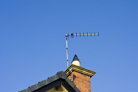 An analogue television aerial attached to a chimney against a blue sky